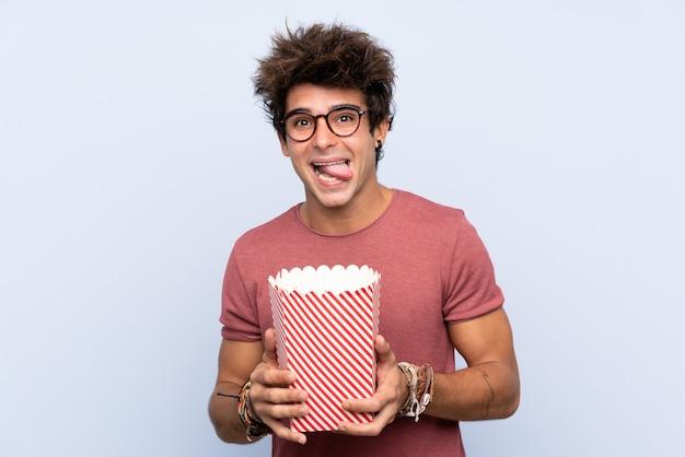 Jonge blanke man over geïsoleerde muur met 3d bril en houden een grote emmer popcorns