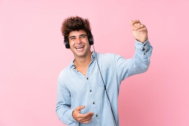 Jonge blanke man over geïsoleerde roze muur met behulp van de mobiele telefoon met koptelefoon en dansen