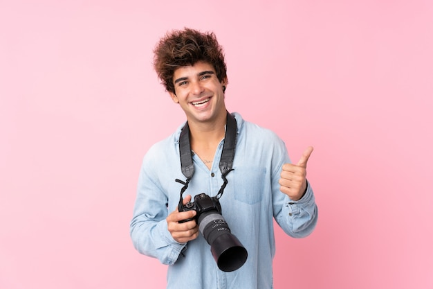 Jonge blanke man over geïsoleerde roze muur met een professionele camera en met duim omhoog