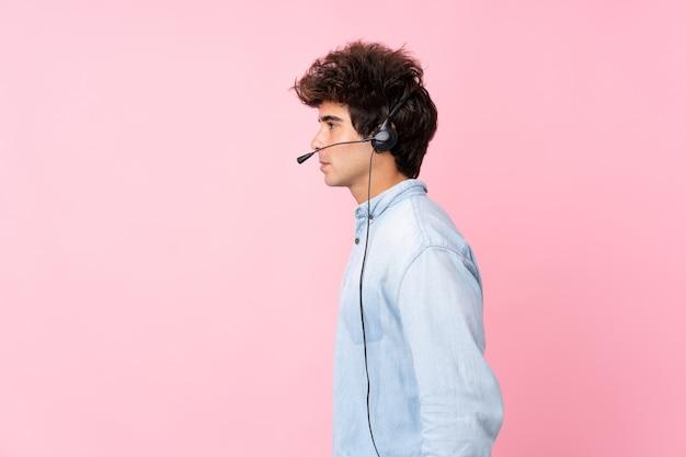 Jonge blanke man over geïsoleerde roze muur werken met hoofdtelefoon