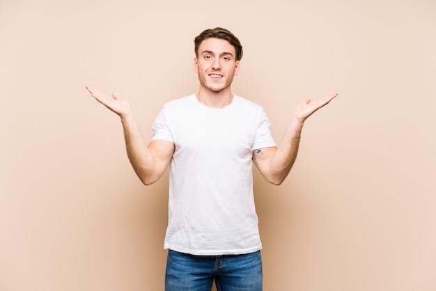 Jonge blanke man poseren geïsoleerd maakt schaal met armen, voelt zich gelukkig en zelfverzekerd.