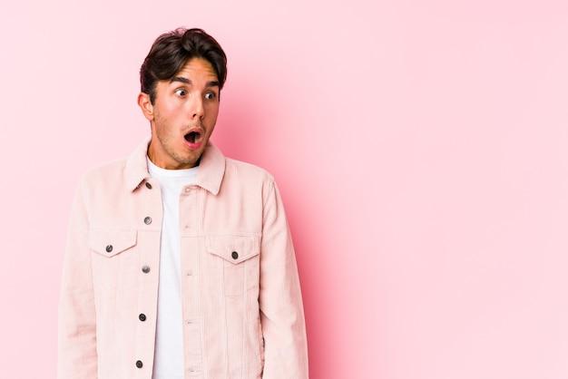 Jonge blanke man poseren in een roze achtergrond geïsoleerd geschokt vanwege iets dat ze heeft gezien.