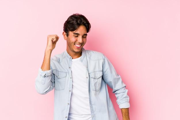 Jonge blanke man poseren in een roze muur dansen en plezier.