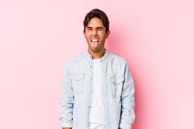 Jonge blanke man poseren in een roze muur geïsoleerde grappige en vriendelijke tong uitsteekt.