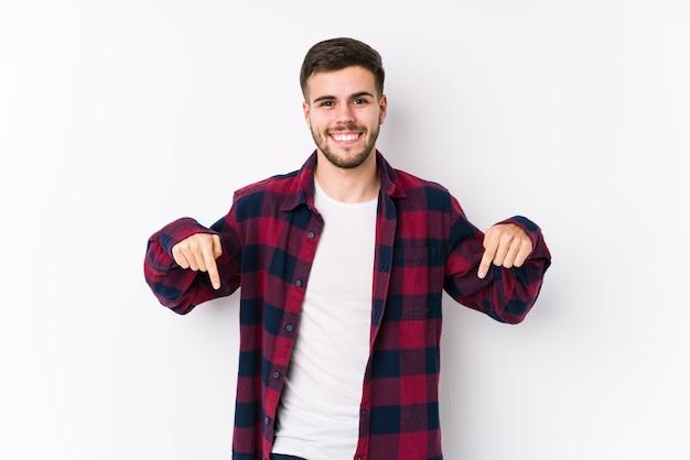 Jonge blanke man poseren in een witte muur geïsoleerde punten naar beneden met vingers, positief gevoel.