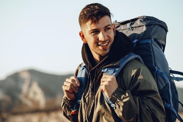 Jonge blanke man reiziger met grote rugzak wandelen in de bergen