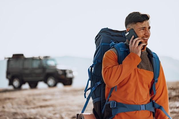 Jonge blanke man reiziger met zijn smartphone