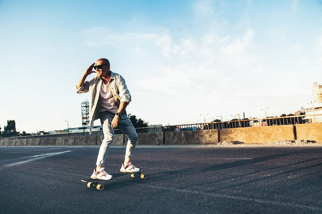 Jonge blanke man rijden op longboard of skateboard, modern schot in filmkorreleffect en vintage stijl.