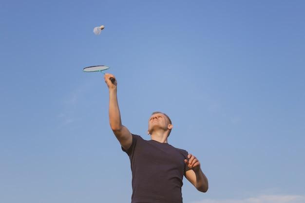 Jonge blanke man speelt badminton op een achtergrond van blauwe hemel.