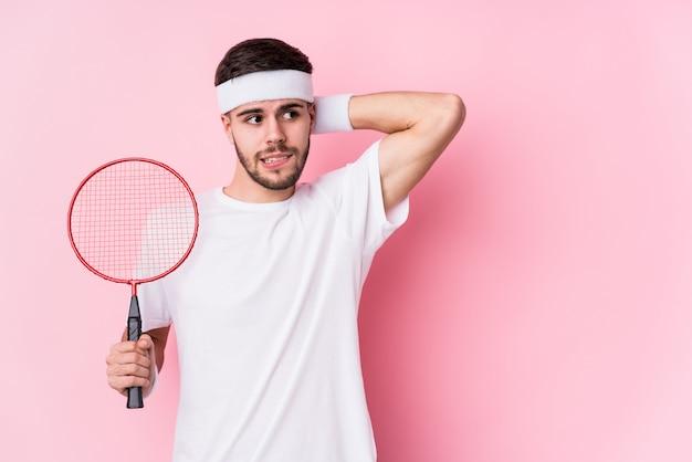 Jonge blanke man spelen badminton geïsoleerd aanraken achterkant van het hoofd, denken en het maken van een keuze.