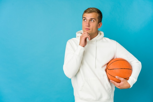 Jonge blanke man spelen basketbal geïsoleerd op blauw opzij kijken met twijfelachtige en sceptische uitdrukking.