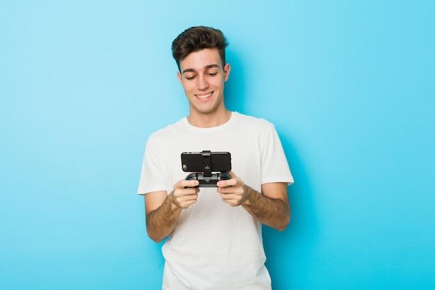 Jonge blanke man spelen videogames met telefoon lacht vertrouwen met gekruiste armen.