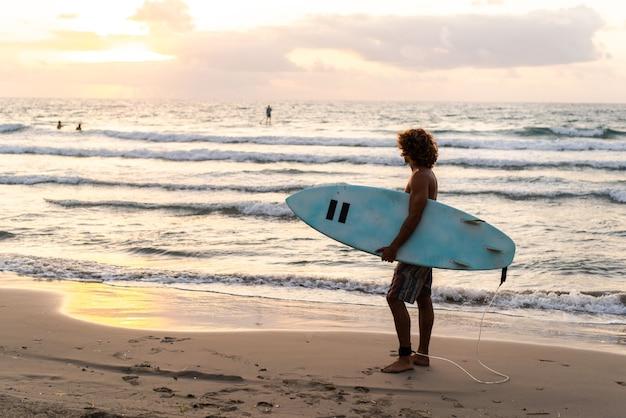 Jonge blanke man staat vroeg op om te surfen bij zonsopgang