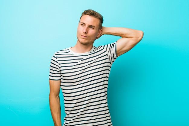 Jonge blanke man tegen een blauwe muur aan te raken achterhoofd, denken en een keuze maken.