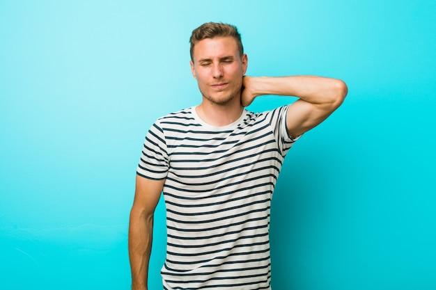 Jonge blanke man tegen een blauwe muur die lijdt aan nekpijn vanwege een zittende levensstijl.
