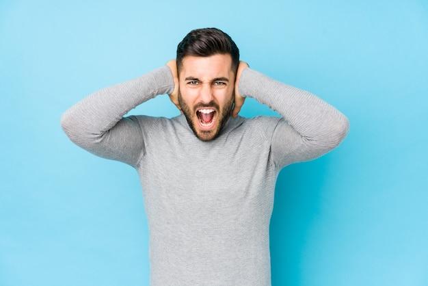 Jonge blanke man tegen een blauwe muur die oren bedekt met handen proberen niet te hard geluid te horen.