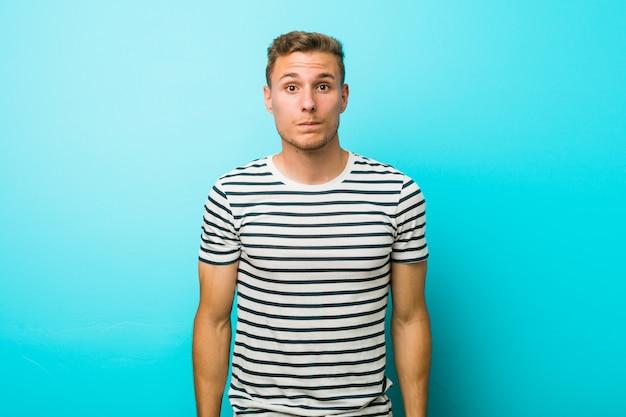 Jonge blanke man tegen een blauwe muur haalt schouders op en verwarde open ogen.