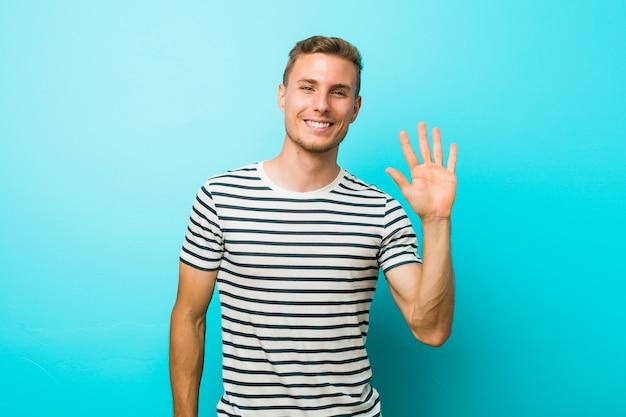 Jonge blanke man tegen een blauwe muur lacht vrolijk met nummer vijf met vingers.