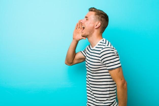 Jonge blanke man tegen een blauwe muur schreeuwen en houden palm in de buurt van geopende mond.