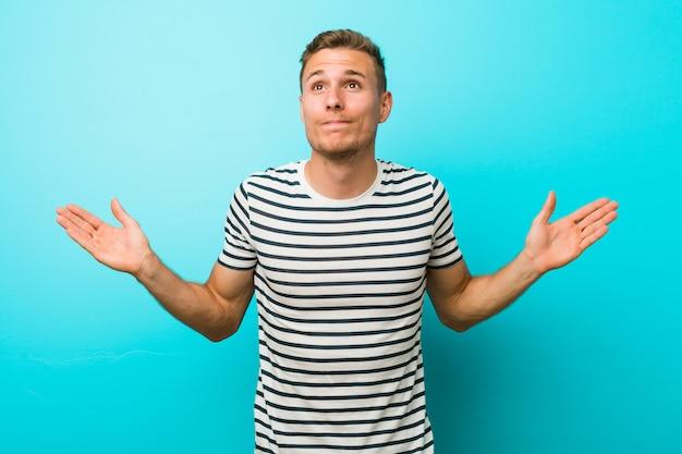 Jonge blanke man tegen een blauwe muur twijfelen en schouders ophalen in verhoor gebaar.