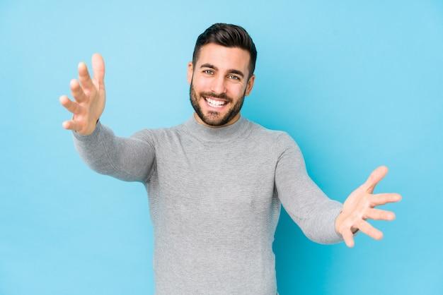 Jonge blanke man tegen een blauwe muur voelt zich vol vertrouwen en geeft een knuffel aan de camera.