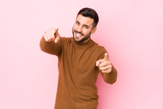 Jonge blanke man tegen een roze muur geïsoleerde vrolijke glimlachen naar voren wijzen.
