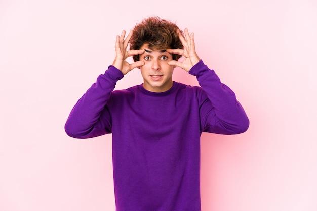 Jonge blanke man tegen een roze muur ogen houden geopend om een succes kans te vinden.