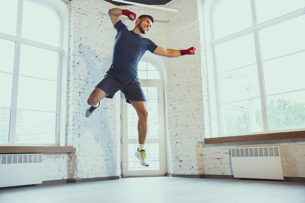 Jonge blanke man training thuis tijdens het opnemen van online cursussen, doinc oefeningen van fitness, aëroob. sportieve isolerende isolatie blijven.