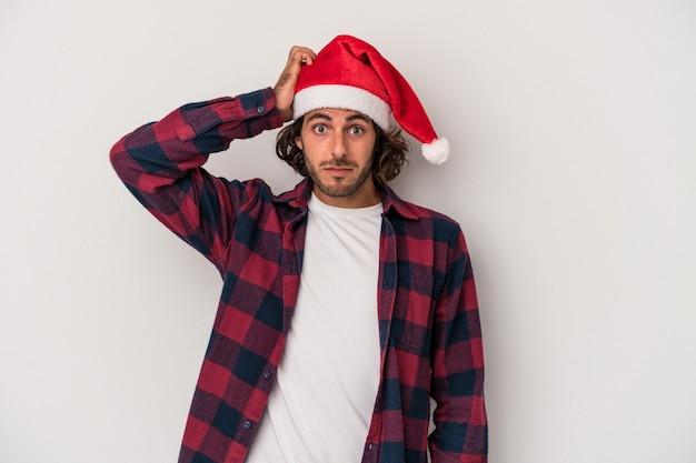 Jonge blanke man viert kerstmis geïsoleerd op een grijze achtergrond geschokt, ze heeft een belangrijke vergadering onthouden.