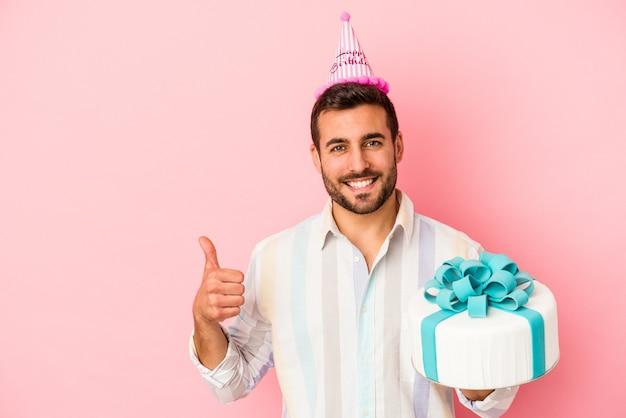 Jonge blanke man viert zijn verjaardag geïsoleerd op roze achtergrond glimlachend en duim opheffen