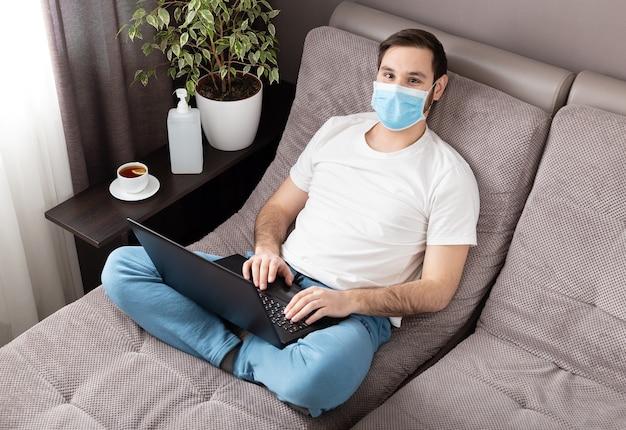 Jonge blanke man werken vanuit huis dragen van beschermend masker met behulp van laptop.