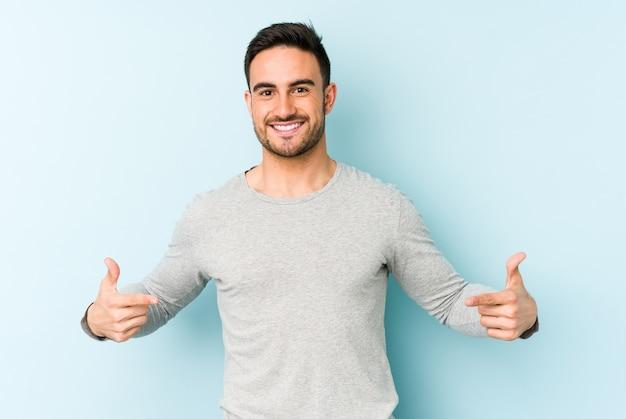 Jonge blanke man wijst naar beneden met vingers, positief gevoel.