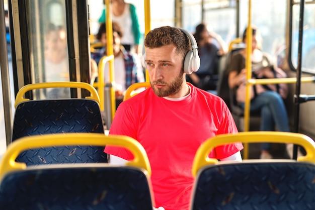 Jonge blanke man zit in een bus, luistert naar de muziek en kijkt door raam.