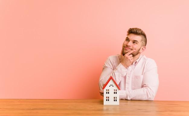 Jonge blanke man zit met een huis pictogram zijwaarts op zoek met twijfelachtige en sceptische uitdrukking.