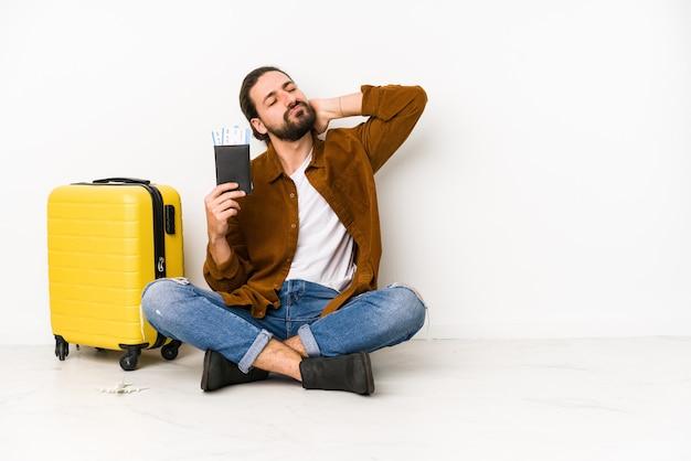Jonge blanke man zit met een paspoort en een koffer geïsoleerd achterhoofd aan te raken, te denken en een keuze te maken.