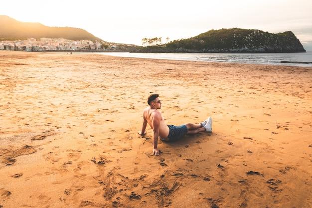 Jonge blanke man zit op het zand van een baskisch strand.