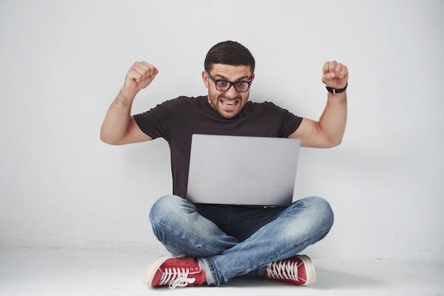 Jonge blanke man zit over witte bakstenen muur met behulp van computer laptop blij in shock met een verrassingsgezicht, bang en opgewonden met angst expressie.