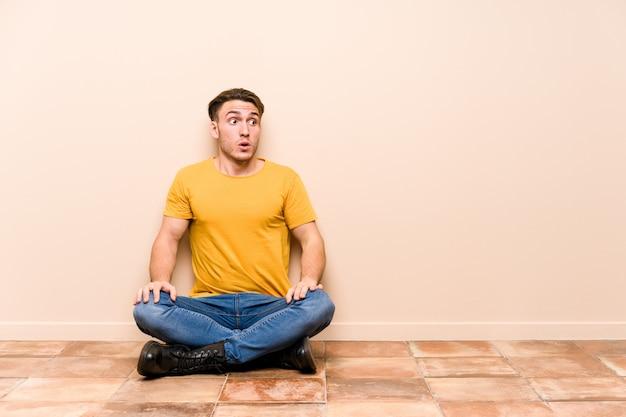 Jonge blanke man zittend op de vloer geïsoleerd geschokt vanwege iets dat ze heeft gezien.