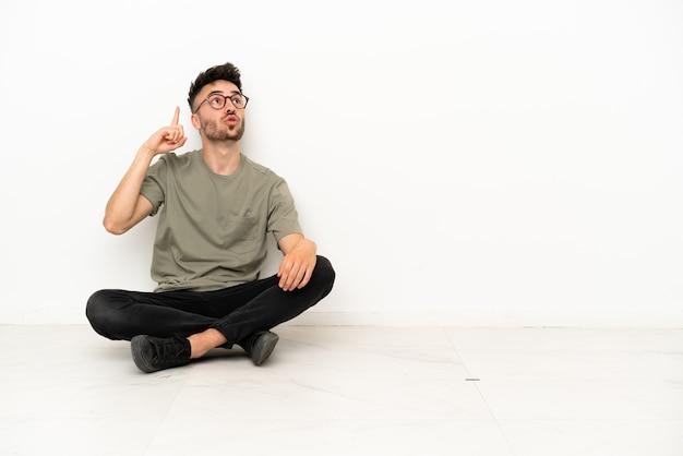 Jonge blanke man zittend op de vloer geïsoleerd op een witte achtergrond denken een idee met de vinger omhoog