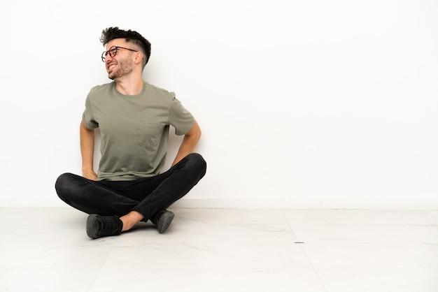 Jonge blanke man zittend op de vloer geïsoleerd op een witte achtergrond die lijdt aan rugpijn omdat hij zijn best heeft gedaan