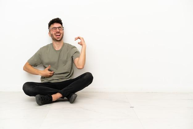 Jonge blanke man zittend op de vloer geïsoleerd op een witte achtergrond gitaar gebaar maken