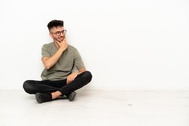 Jonge blanke man zittend op de vloer geïsoleerd op een witte achtergrond kijkend naar de zijkant