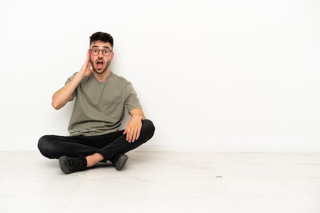 Jonge blanke man zittend op de vloer geïsoleerd op een witte achtergrond met verrassing en geschokte gezichtsuitdrukking