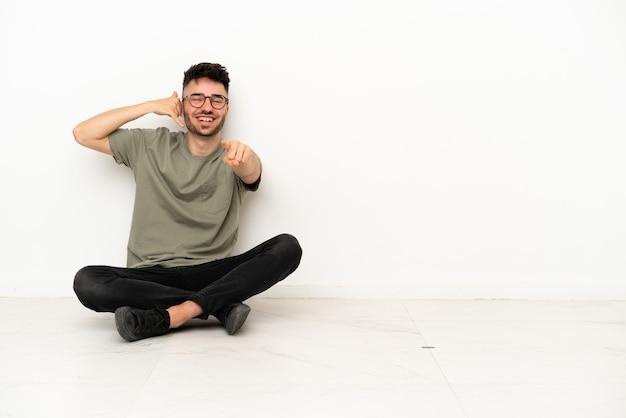 Jonge blanke man zittend op de vloer geïsoleerd op een witte achtergrond telefoon gebaar maken en naar voren wijzen