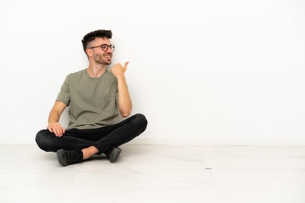 Jonge blanke man zittend op de vloer geïsoleerd op een witte achtergrond wijzend naar de zijkant om een product te presenteren