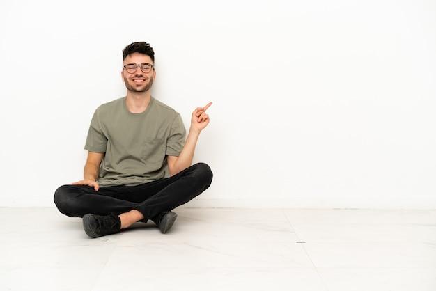 Jonge blanke man zittend op de vloer geïsoleerd op een witte achtergrond wijzende vinger naar de zijkant