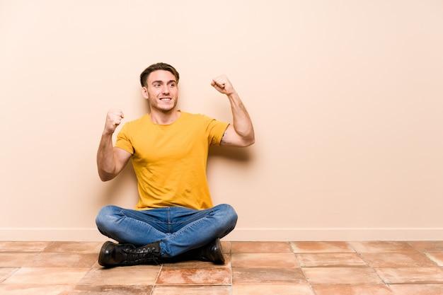 Jonge blanke man zittend op de vloer geïsoleerd verhogen vuist na een overwinning, winnaar concept.