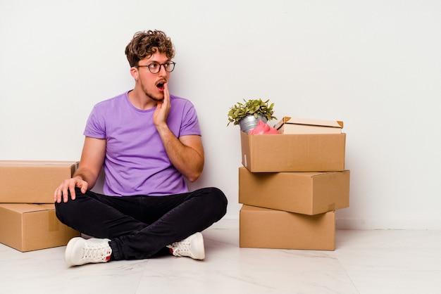 Jonge blanke man zittend op de vloer klaar om te bewegen geïsoleerd op een witte achtergrond zegt een geheim heet remmend nieuws en kijkt opzij