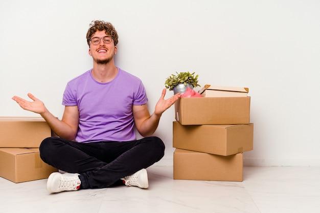 Jonge blanke man zittend op de vloer klaar om te verhuizen geïsoleerd op een witte achtergrond met een welkome uitdrukking.