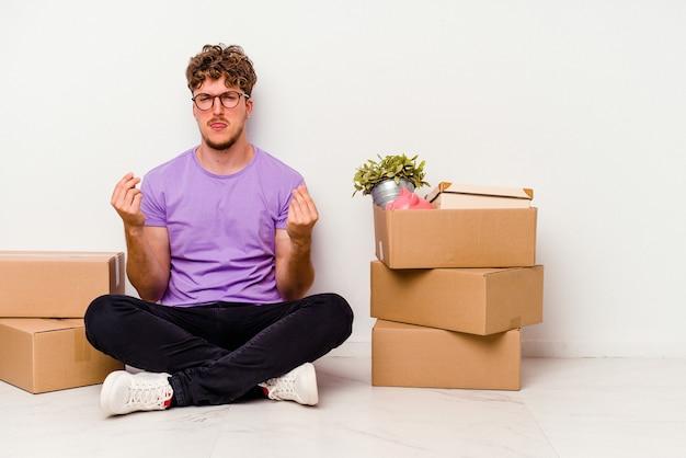 Jonge blanke man zittend op de vloer klaar om te verhuizen geïsoleerd op een witte muur waaruit blijkt dat ze geen geld heeft.